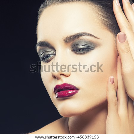 Beauty fashion portrait of caucasian brunette woman with wet red lipstick and arms touching face. Isolated on black background. Toned