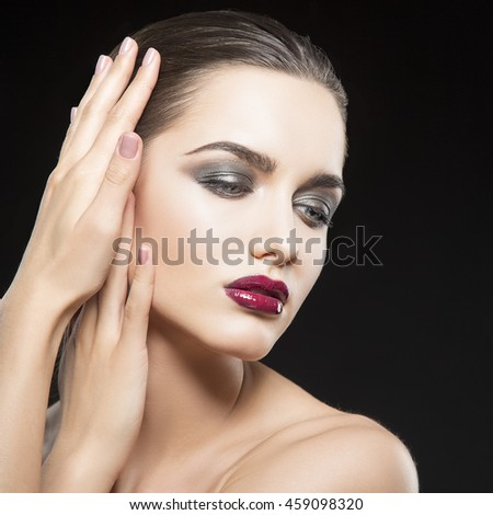 Beauty fashion portrait of caucasian brunette woman with wet red lipstick and arms touching face. Isolated on black background. - stock photo