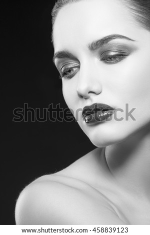 Beauty fashion portrait of caucasian brunette woman with wet red lipstick. Isolated on black background. Black and white