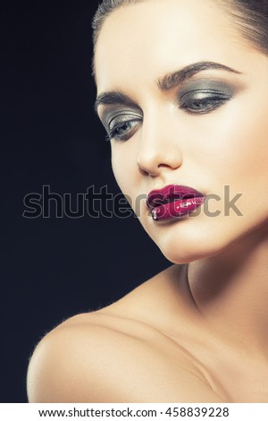 Beauty fashion portrait of caucasian brunette woman with wet red lipstick. Isolated on black background. Toned - stock photo