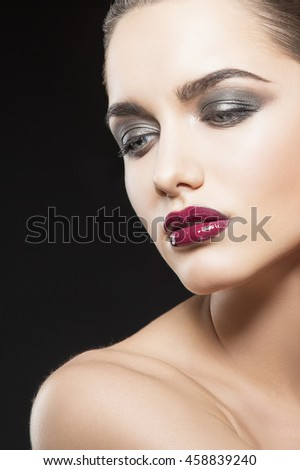 Beauty fashion portrait of caucasian brunette woman with wet red lipstick. Isolated on black background. - stock photo