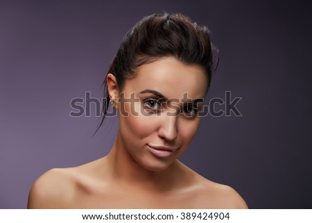 Beauty Fashion Portrait of Caucasian Young Girl with Natural Nude Make Up with brown eyes and shoulders on purple gradient background.  - stock photo