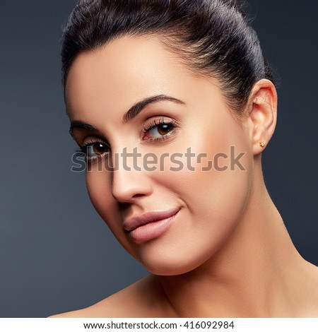 Beauty Fashion Portrait of Smiling Caucasian Young Girl with Natural Nude Make Up. Close up. Brown eyes and open shoulders. On grey gradient background. Toned. - stock photo