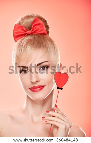 Beauty fashion portrait woman smiling with red heart. Valentines Day, love. Sensual attractive pretty nude blonde sexy girl, Pinup hairstyle, bow. Unusual emotional playful. Romantic, retro vintage  - stock photo