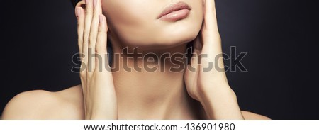 Beauty fashion vogue style face of caucasian brunette with elegant make-up, blue eyes, natural lips touching perfect skin. Close-up studio portrait isolated. Black background with grey spot. Toned. - stock photo
