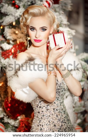Beauty fashion woman Christmas background new year tree. Vogue style sexy girl.  Gorgeous female in luxury fur at Xmas party. Luxury life concept. Retro style lady - stock photo