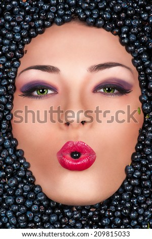 Beauty fashion woman in face with blueberry, berry in the mouth