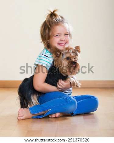 Beauty female child playing with charming Yorkie at home - stock photo