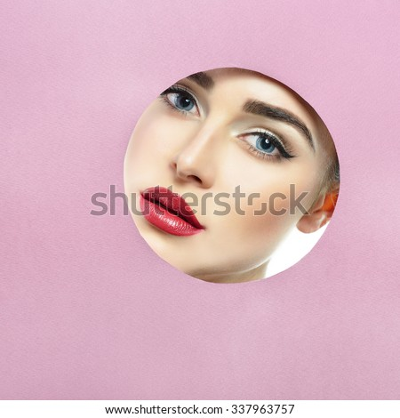 Beauty female portait. Young beautiful woman look out of circle in purple paper. Girl's face in round paper frame with copyspace for your message