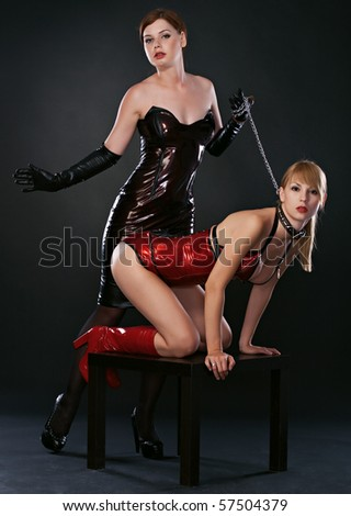 beauty fetish bdsm woman in dresses on black background - stock photo