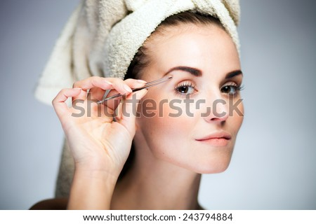 Beauty fresh model girl shaping eyebrows with tweezer - stock photo