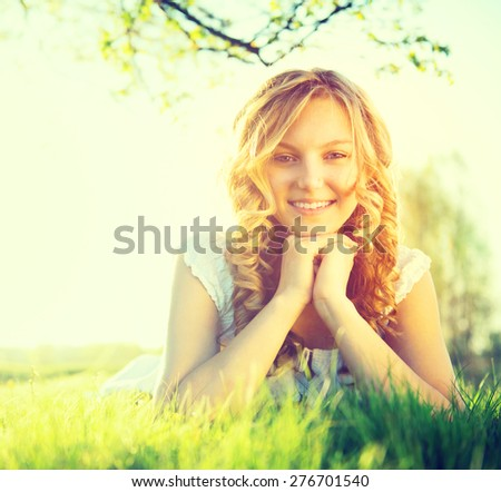 Beauty Fresh Romantic Girl lying on summer field Outdoors. Nature. Beautiful Model young Woman with long curly hair Smiling. Cute Teenage Girl lying on grass. Meadow. Grassland. Allergy free. Sunshine - stock photo
