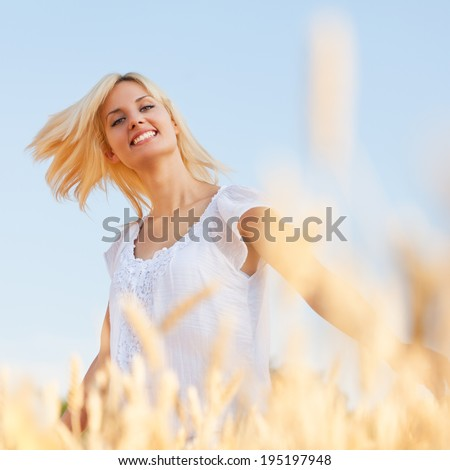 Beauty Fresh Romantic Girl Outdoors. Nature.Beautiful Model young Woman with long blond hair on a Field Smiling. - stock photo