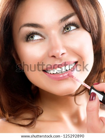 Beauty Girl Applying Lipgloss. Makeup. Beautiful Woman's Face. Apply Make-up. Healthy Smile. White Teeth.
