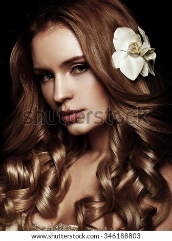 Beauty Girl. Beautiful blonde with long wavy hair. Flower in the hair. Evening make-up. Clean healthy skin. Black background. Looking at camera.