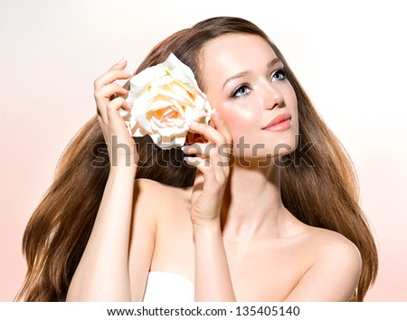 Beauty Girl. Beautiful Model with Rose Flower Touching her Face. Healthy Long Hair and Clear Skin. Youth. Isolated on White Background. Blowing Hair. Skincare concept - stock photo