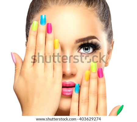 Beauty Girl Face with Colorful Nail polish. Colourful Studio Shot of young Woman. Vivid Colors. Colourful Manicure and fashion Makeup. Rainbow Colors. Beautiful lady touching face. Isolated on white - stock photo