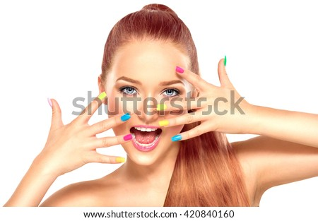 Beauty Girl Face with Colorful Nail polish. Colourful Studio Shot of young Woman. Vivid Colors. Colourful Manicure and fashion Makeup. Rainbow Color. Beautiful lady touching her face isolated on white - stock photo