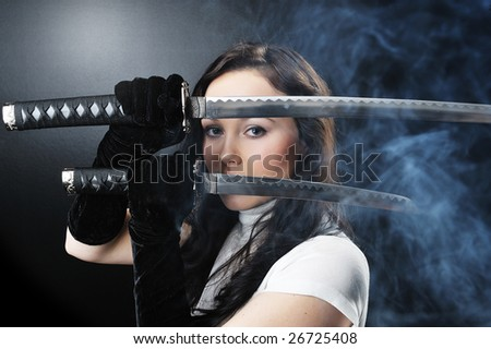 beauty girl holding in her hands two katana - stock photo