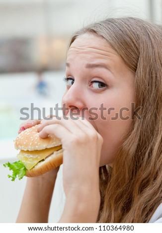 beauty girl in cafe eating hamburger - stock photo