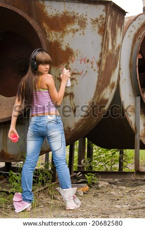 beauty girl in headphones painting on constructions - stock photo