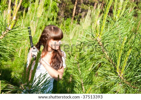 beauty girl in white dress with gun on nature background - stock photo