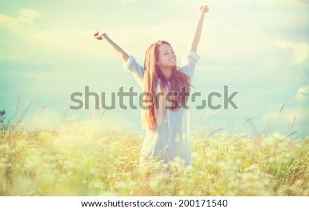 Beauty Girl Outdoors enjoying nature. Beautiful Teenage Model girl in white dress having fun on summer Field with blooming flowers, Sun Light. Glow Sun. Free Happy Woman. Toned in warm colors - stock photo