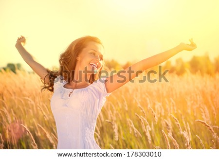 Beauty Girl Outdoors enjoying nature. Beautiful Teenage Model girl in white dress running on the Spring Field, Sun Light. Glow Sun. Free Happy Woman. Toned in warm colors.  - stock photo
