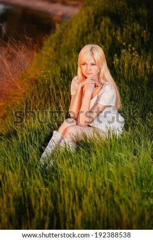 Beauty Girl Outdoors enjoying nature. Beautiful Teenage Model girl in white dress sitting on green grass on the river bank at sunset. Sun Light. bride enjoying walking in spring forest.