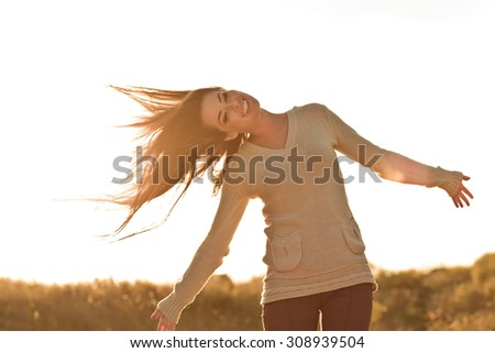 Beauty Girl Outdoors enjoying nature. Beautiful Teenage Model girl with long healthy blowing hair running on the Spring Field, Sun Light.  Toned in warm colors  - stock photo