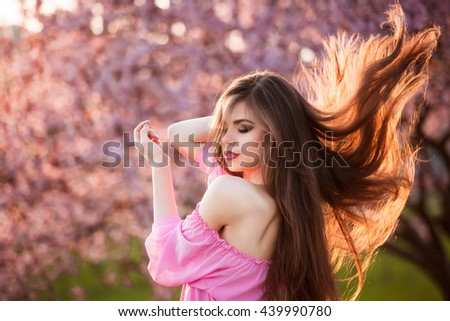 Beauty Girl Outdoors enjoying nature. Beautiful Teenage Model girl with long healthy blowing hair running in blossom park, Sun Light. Glow Sun. Free Happy Woman. - stock photo