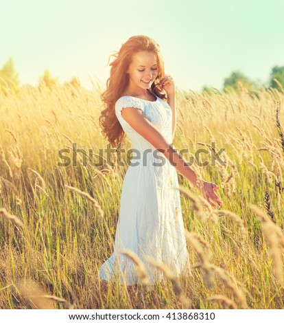Beauty Girl Outdoors enjoying nature. Beautiful Teenage Model girl with perfect long curly hair, in white dress standing on the Spring Field, Raising hands in Sun Light - stock photo