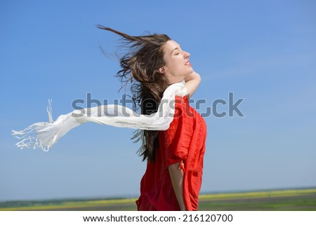 Beauty Girl Outdoors enjoying nature. Happy young woman holding white scarf with opened arms expressing freedom, outdoor shot against blue sky. - stock photo
