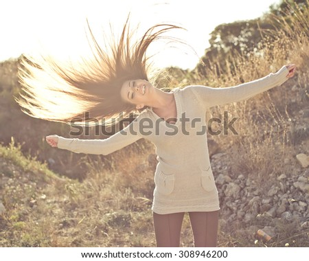 Beauty Girl Outdoors enjoying nature.Playing hair wind.Glow Sun. Free Happy Woman. Toned in warm colors - stock photo