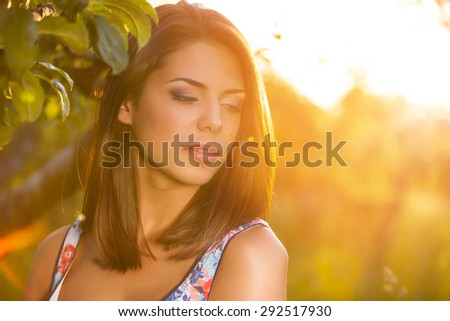 Beauty Girl Outdoors enjoying nature. Sun Light. Glow Sun. Free Happy Woman. Toned in warm colors