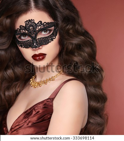 Beauty girl portrait in venetian lace mask. Wavy hairstyle. Healthy long hair. Sensual lips. Makeup. Fashion beautiful woman in coffee brown elegant dress.