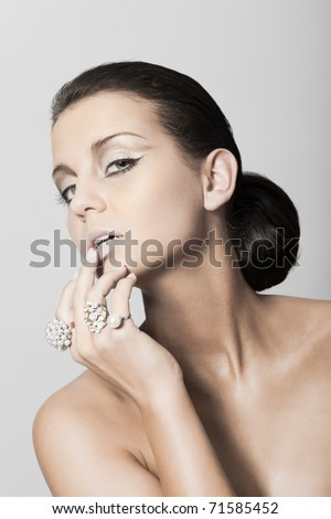 Beauty girl posing with rings on hand touching lips - stock photo