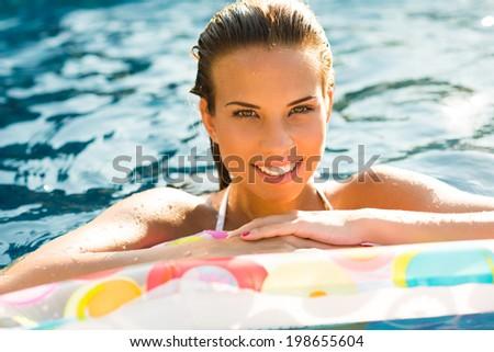 Beauty girl relaxing in pool using mattress - stock photo