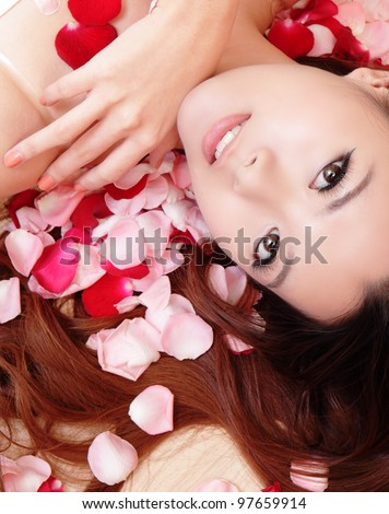 beauty Girl smiling face and hand touch her face close up with red rose background, model is a asian beauty