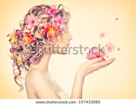 Beauty girl takes beautiful flowers in her hands. Blowing flower. Hairstyle with flowers.  Fantasy girl portrait in pastel colors. Summer fairy portrait. Long permed hair. - stock photo