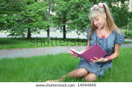 beauty girl with book on green grass