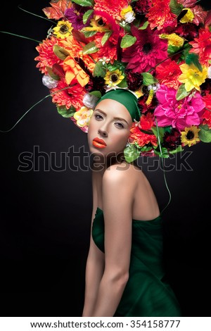 Beauty Girl with Flowers Hairstyle. Beautiful Young Woman Portrait with Summer orange Flowers. Big hat with flowers, Fashion Makeup. Orange lip gloss.