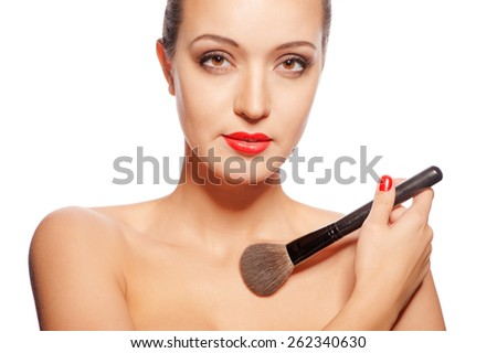 Beauty Girl with Makeup Brush. Bright Holiday Make-up for Brunette Woman with Brown Eyes. Bright red lips. Beautiful Face. Makeover. Perfect Skin. Applying Makeup - stock photo