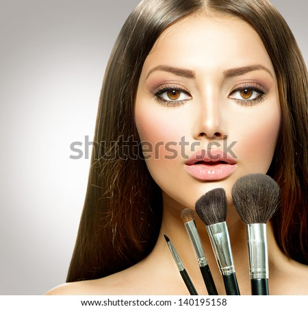 Beauty Girl with Makeup Brushes. Natural Make-up for Brunette Woman with Brown Eyes. Beautiful Face. Makeover. Perfect Skin. Applying Makeup - stock photo