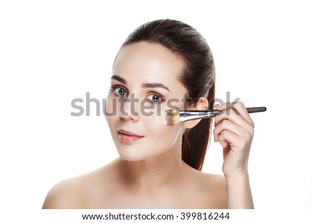 Beauty Girl with Makeup Brushes. Natural Makeup for Brunette Woman with blue Eyes. Beautiful Face. Makeover. Perfect Skin. Applying Make-up. Ideal for commercial  - stock photo