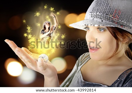 Beauty girl with silver hat holding magic disco ball with light effect and girl dancer in her palm