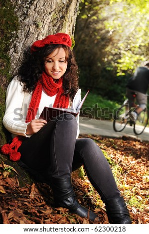 Beauty gorgeous autumn girl sitting in nature beside the tree and reading the book - stock photo