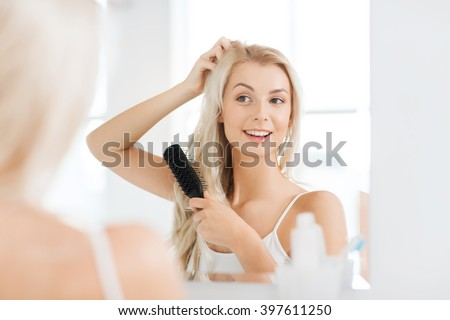beauty, grooming and people concept - smiling young woman looking to mirror and brushing hair with comb at home bathroom - stock photo