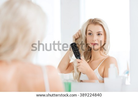 beauty, grooming, hair care and people concept - smiling young woman looking to mirror and brushing hair with comb at home bathroom - stock photo
