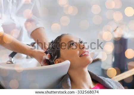 beauty, hair care and people concept - happy young woman with hairdresser washing head at hair salon over holidays lights - stock photo